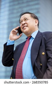 Asian businessman in suit talking on smart phone