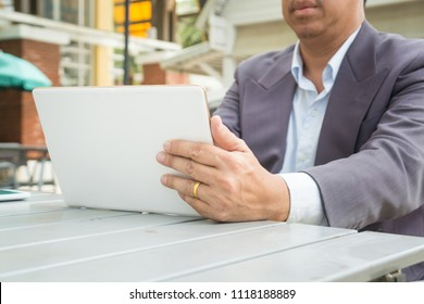Asian Businessman in Suit use Digital Wireless Tablet outdoor in Public with Wifi connection as Modern Business and Technology Lifestyle