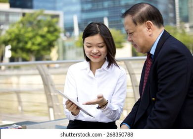 Asian businessman in suit and young female executive holding table brainstorming
