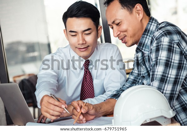 Asian businessman talking about detail plan building with engineer