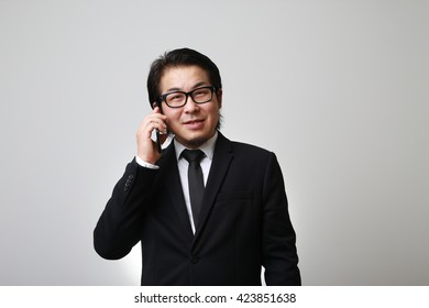 The Asian businessman talking with his smartphone.