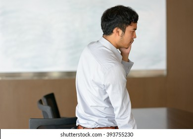 Asian businessman talking on mobile phone at office