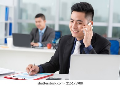 Asian businessman talking on the phone and writing while his colleague working in background