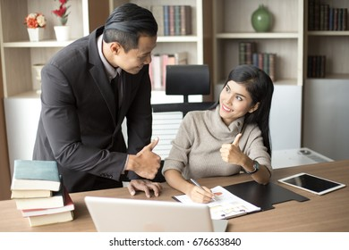Asian businessman training to secretary about how to work at office, man with relax time concept.