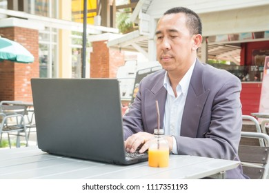 Asian Businessman typing on Notebook or Laptop Computer on Table in Outdoor Public as Mobile Workplace and Modern Lifestyle