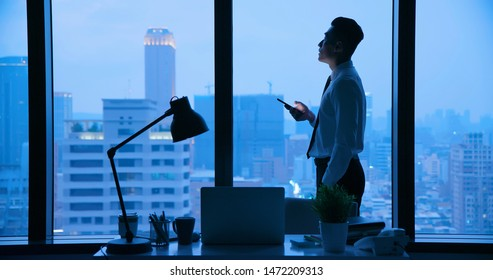 Asian businessman use smartphone at night in the office