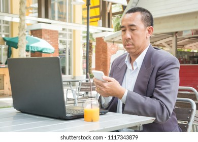 Asian Businessman use Wireless Digital Smartphone and Laptop or Notebook Computer in Public Place as Modern Business and Technology Lifestyle