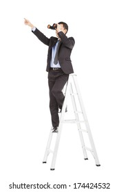 asian businessman using binoculars standing  on stair