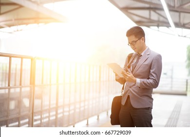 Asian businessman using digital tablet pc at railway platform, with beautiful sun flare at background.