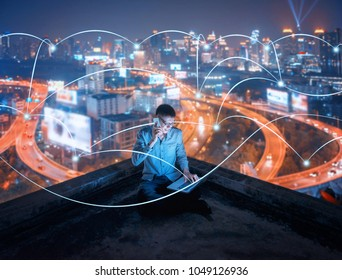 Asian businessman using phone and laptop on rooftop with social connection lines in smart city at night