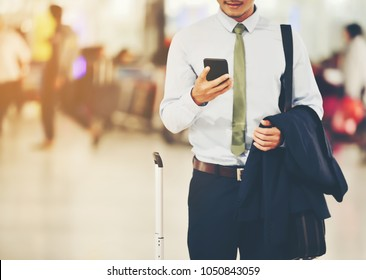 An Asian businessman is using a smartphone to get in business while waiting for a trip in the airport.This image is Soft focus.