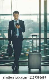 An Asian businessman is using a smartphone to get in business while waiting for a trip in the airport.
