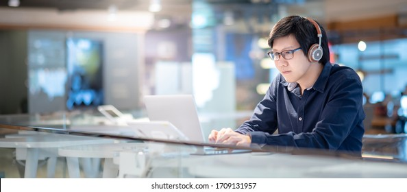 Asian businessman wearing headphones listening to music while working with laptop computer at home office. Male office worker searching information on internet platform. Work from anywhere concept