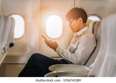 asian businessman in white shirt sitting by window in airplane using smartphone during business trip travelling