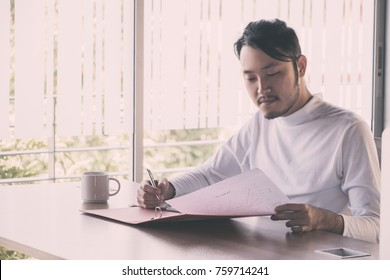 Asian businessman who sitting work in feeling happy at the office with daylight from window and blur garden background.