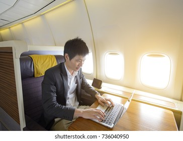 Asian businessman working on laptop in the luxury airplane