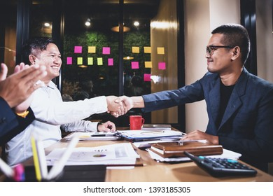 Asian businessmen discussing work sitting in office conference room at night scene, graph analysis and teamwork concept