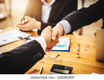 Asian businessmen friends join hands shaking after finding a summary of the shortcomings and direct selling business problems that are experiencing.