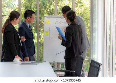 Asian businessmen meeting teamwork, planning and analyze performance By writing graps on the board at workplace, to business concept.