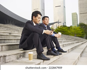 asian businessmen sitting on steps and talking.