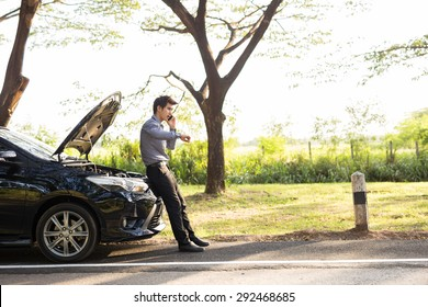 Asian businessmen talking on a cell phone by a broken car On Country Road Phoning For Help.Broken Car On The Road in During rush hour .