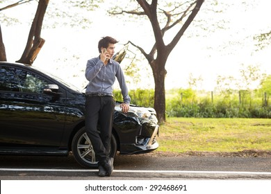 Asian businessmen talking on a cell phone broken car On Country Road Phoning For Help.Broken Car On The Road in During rush hour .