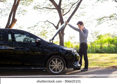 Asian businessmen talking on a cell phone by a broken car On Country Road Phoning For Help, Man broken car.Broken Car On The Road in During rush hour .