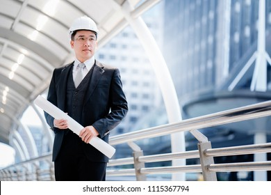 Asian Businessmen who specialize in construction design. Standing in a suit, carrying a work plan with pride in management. To succeed And earned him various awards. Plenty to the company.