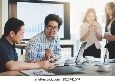Asian businesspeople discussing and brainstorm with young freelance man in meeting room. Business company co-operate with outsource worker concept.