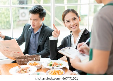 Asian businesspeople are on break for lunch at a restaurant.She was ordering food from a waiter