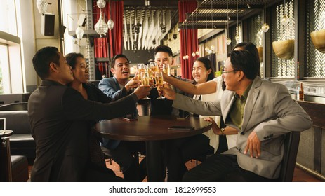 asian businesspeople toasting and clinking wine or champagne together to celebrate friendship in business lounge and club