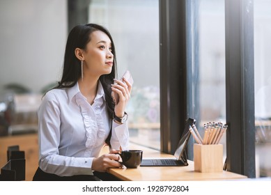 Asian businesswoman analyze ideas looking out of a window at coffee shop.