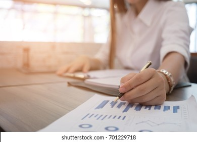 asian businesswoman analyze market chart at workplace.  young female entrepreneur woman working with business document at office. analytic financial accounting graph plan report.  paperwork on table.