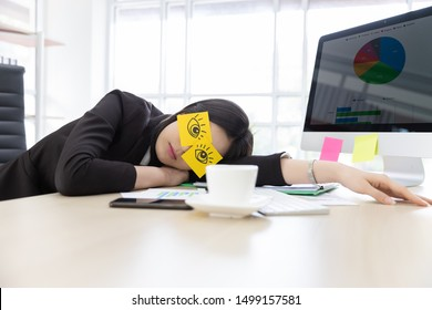 Asian businesswoman in black suit tired frustrated from working at the computer screen. She covering eyes, fake eyes with note pad and Sleeping in desk at office building.