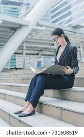 Asian businesswoman is checking report document on new project prepare for meet customer while sitting on stair outside office, business outdoor concept
