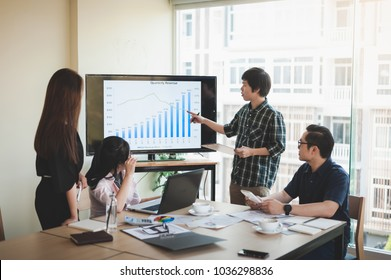 Asian businesswoman discussing and brainstorm with young freelance man in meeting room. Business company co-operate with outsource worker concept.