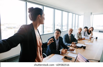 Asian businesswoman explaining new business strategy to coworkers sitting around table in conference room. Businesspeople during presentation in board room.
