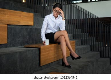 Asian businesswoman feel despair with bad news about business financial of company bankruptcy holding a coffee cup sitting on staircase at the office- woman office worker and businesswoman concept