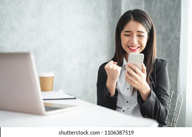Asian businesswoman in formal suit in office happy and cheerful during using smartphone and working