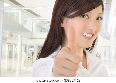 Asian businesswoman gesture with thumb up on white background.