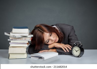 Asian businesswoman get tired reading many books on gray background