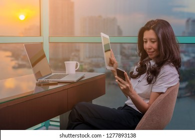 Asian businesswoman having business call in office, her workplace, writing down some information. Woman using Laptop, Tablet and looking at smartphone screen.