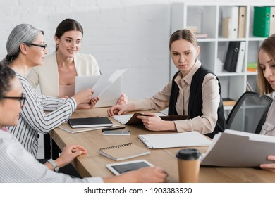 asian businesswoman holding document near happy team leader and coworkers in office