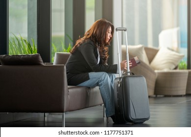 Asian businesswoman at international airport, looking passport and waiting for her flight.