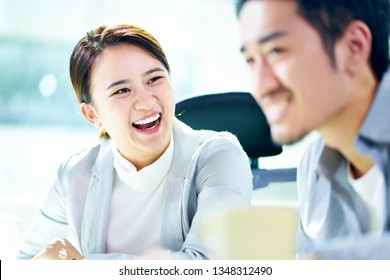 asian businesswoman laughing during meeting with male colleague in office.