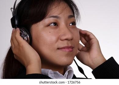 Asian businesswoman listening music