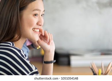 Asian businesswoman looking at laptop computer and smiling face with happy emotion from good news of business success