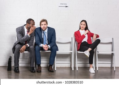 asian businesswoman looking at multicultural businessmen gossiping while waiting for job interview
