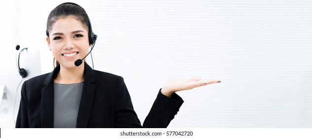 Asian businesswoman as an operator in call center making open hand (palm) gesture - panoramic banner with copy space