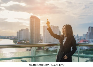 Asian businesswoman pointing on sky and leave space for adding your content and background blur building skyscrapers at sunset. (vintage color tone, advertise concept)